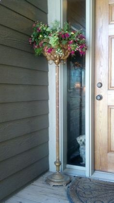 Repurposed lamp stand becomes the perfect welcome garden for your front door.