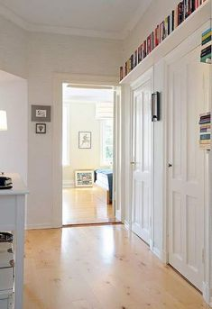 like the idea of shelves at above-doorway-level all around a room -- Drew needs book storage! Bookcase Door, Bookshelves, Barrister Bookcase, Small Apartments, Small Spaces, Comic Book Storage, Ceiling Shelves, Shelving, Home Libraries