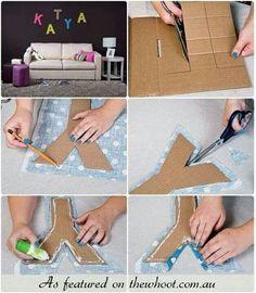 Je naam in kartonnen letters en dan versieren met lapjes stof en stickertjes enz. en dan op een groot stuk karton plakken, die ook versierd is.