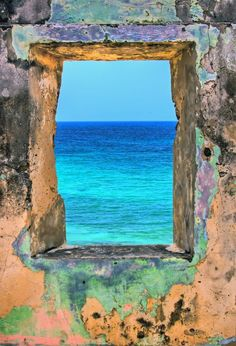 Stone window opening to the blue sea. Shop the luxury Matthew Williamson beachwear collection on our online boutique.