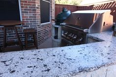 L-shaped outdoor kitchen with stainless BBQ, green egg, and granite countertops. By Outdoor Signature in Argyle, TX