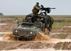 A Land Rover piles through the mire at Salisbury Plain, in Wiltshire, during a live firing...