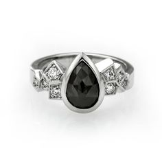 Unique custom made engagement ring with black pear shaped diamond.