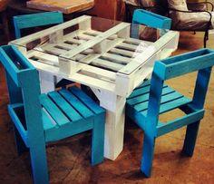 une table blanche et des chaises bleues en palettes de bois