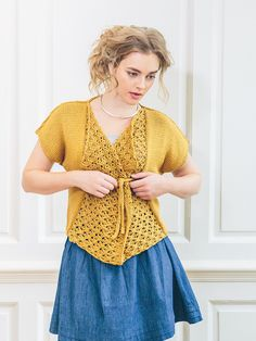 Ran - Knit this women's lace stich draped wrap over cardigan from the Cotton Lustre Collection, a design by Sarah Hatton using the exquisite yarn Cotton Lustre (cotton, modal and linen). The main body is knitted in stocking stitch with short grown on sleeves. The front borders are picked up and worked in a beautiful lace pattern to create a drape. The i cord fastening makes this a very flattering piece. This knitting pattern has a two star difficulty rating.