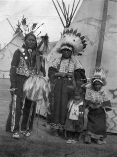 A Native American (Dakota) man, identified as Poor Wolf, poses with his wife and two children in front of tepees. - 1880/1910