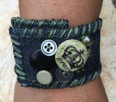 **SALE ITEM** (25% off original price $22.00)  This is a handmade cuff bracelet with new and vintage buttons that are hand sewn individually and secure. The materials are upcycled denim from jeans with machine sewn sides. To accent the cuff, I have hand-stitched the ends and sides with embroidery thread and completed the cuff with a button snap closure. I have added beads within the design as an added touch.  The cuff is approximately 1 1/2 wide by 9 long. The total closure length is…