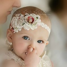 This beautiful headband features two shabby chic flowers on an elastic headband. It is topped with a luxurious eye catching rhinestone between the two flowers. The flowers are felt backed for comfort. Simple and yet elegant, sure to be a real head turner!! Pair it with one of our adorable lace petti rompers for a complete look.