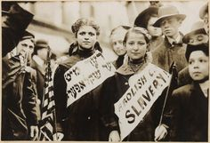 """Protest against child labor, New York City, May 1, 1909 (Labor Day). Two young girls proudly wear sashes calling for an end to child labor, referring to the practice as """"child slavery."""" The signs are written in both English and Hebrew. Jewish immigrants, forced out of Russia and Eastern Europe because of pogroms and anti-Semitic laws, came to New York City in large numbers. Many immigrant Jews worked in the garment industry, a field rife with unfair labor practices. The New York City garment"""