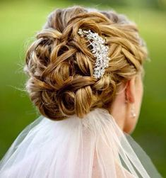 Stunning wedding hair, silver head piece finished off with a veil under the bun