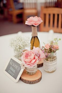 <3 centre de table <3 mariage rustique avec rondins de bois et divers contenants en verre avec pivoines et roses