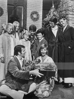 The cast of the television series 'The Brady Bunch' stands and watches American actors Robert Reed and Florence Henderson exchange wrapped Christmas presents during the episode 'A Very Brady Christmas'. From left to right, Eve Plumb, Maureen McCormick, Susan Olsen, Christopher Knight, Mike Lookinland, Barry Williams, and Ann B Davis.