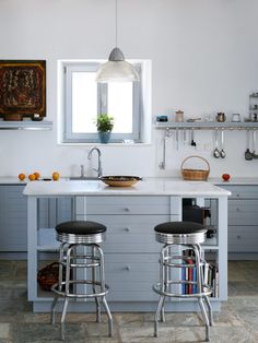 A pair of retro bar stools offers seating at a kitchen island and can easily be removed during meal prep -- #kitchens #decor #cleankitchen
