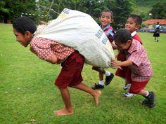 Na het maaien van het gazon op school hielpen de kinderen mee het gras in zakken op te ruimen, naar het strand te brengen en bij het andere afval te gooien.