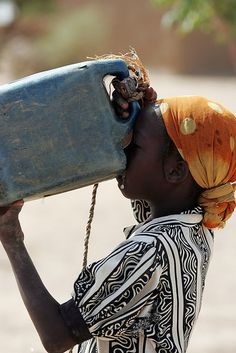 A young girl drinks deeply from a plastic water container. In Chad, Africa, water is scarce and often contaminated.