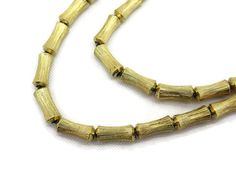 A vintage beaded necklace, with gold tone bamboo shaped beads, strung on a chain. May be unsigned Goldette.  No marks. Measures about 31.25 long.