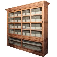 British Colonial shop cabinet, India  c. 1880-1900. Faded teak wood, with sliding glass doors to both top and bottom.