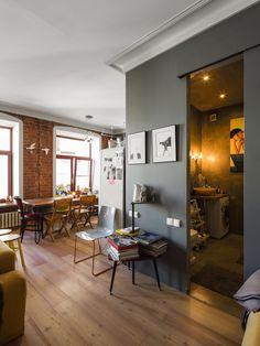 Квартира с кирпичными стенами и разноформатной мебелью на последнем этаже дореволюционного дома