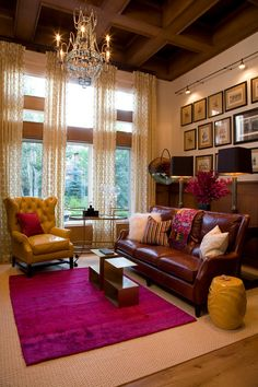 In our front room: vaulted ceilings, tall windows, gallery wall. Love the sheer drapes and bold, grounding rug!
