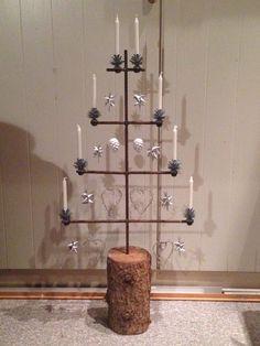 Lille juletræ lavet i jern, pyntet med sølvstjerner og hvide lys.