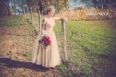 Beautiful country wedding image of bride along fence - Image by JNP