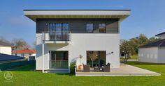 Modernes Stadthaus Buchholz von Baufritz. Kombinierte Fassadengestaltung mit weißem Mineralputz und grauer Holzverschalung.