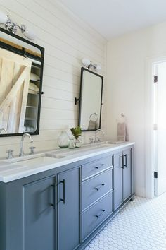 Blue gray bathroom cabinet. Bathroom features blue gray bathroom cabinets and a shiplap accent wall lined with a blue gray double washstand adorned with long bronze pulls topped with striped marble fitted with two sinks and polished nickel high arc faucets placed under Restoration Hardware Industrial Rivet Pivot Mirrors lit by Vintage English Oval Double Sconces alongside a white hex tiled floor finished with white grout. Kate Marker Interiors.