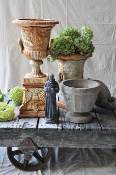 Mixing vintage urns and pots in among planted material can really liven up the garden.