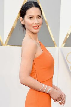 Munn wears her one-shoulder gown with a serpent diamond bracelet by Forevermark.