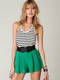 Green shorts with white and black striped shirt and black belt