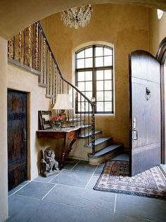 Love all the details in this entry...slate floor, staircase and railings, window, chandelier, painted walls, accessories and rug.