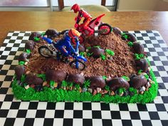 Dirt Bike Cake for my 4 year old. I used a 11x15 casserole pan and also baked some cake in a bread pan to use for the mounds.  The dirt is crushed up peanut butter cups (tastier than graham crackers and doesn't get soggy!) I added chocolate rocks I bought off amazon, chocolate donuts for the tire borders, and piped on some grass.  He loved the cake but I wish the dirt bikes were smaller, they looked ridiculously huge on the cake!