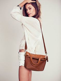 Convertible Vegan Crossbody | Attractive and versatile vegan leather crossbody with detachable shoulder strap that hooks to multiple locations for convertible styling options. Top folds down for a new, smaller shape. Lined interior with storage compartments and snap closure. By Free People