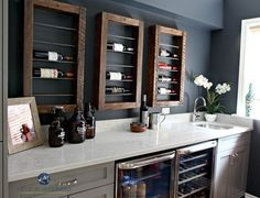 Home bar with wine display and storage, beer and wine fridge. Bianco Drift quart countertop, painted gray cabinets and Sherwin Williams Cyberspace. Kylie M INteriors E-design