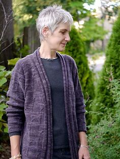 This relaxed, tunic-length cardigan in five sizes features a soft shape and a subtle fabric texture, with pleated borders along the center front edges, which rise to form a standing collar around the neck. Fit is softly oversized; this design is best worked in a softly spun yarn to encourage a luxurious drape throughout the sweater body. All pieces are worked flat, bottom up, and seamed afterward. Substituting yarn and/or needles may result in an overall variation in sizeShown top to bo...