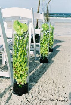 Aisle decor for a beach wedding using tall cylinder vase with orchids immersed in water.