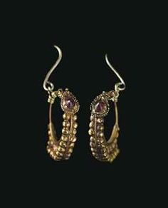 A PAIR OF ROMAN GOLD AND GARNET EARRINGS  CIRCA 1ST CENTURY B.C.-1ST CENTURY A.D.  Each formed from a plain hoop tapering to a hook-and-loop closure, the lower portion decorated with a row of single granules above a double row of granules centered by a plain wire, fronted by a drop-shaped element bordered by granulation and topped with a single granule, set with a peaked garnet; joined to modern gold earwires Each: 7/8 in. (2.2 cm.) wide (2)