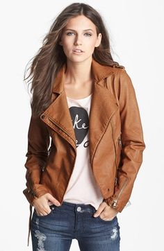 Graphic tee, brown leather jacket, distressed jeans.