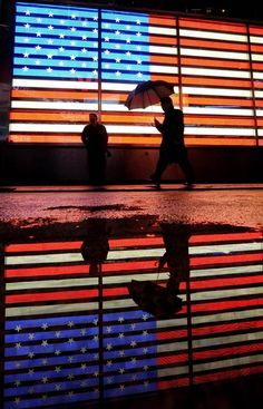People are reflected in a puddle as they walk past a neon American flag in New York's Times Square in December 2011.