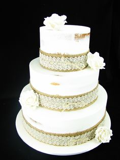 A rustic style wedding cake made of white chocolate mud cake with buttercream in a semi-naked finish. The roses are hand made from fondant. — at Oneday Estate Winery & Function Centre.
