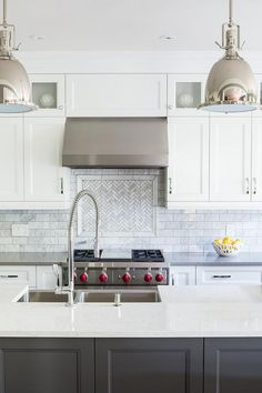 Dark gray lower island cabinets paired with white stacked uppers, chrome finishings, and gray Cambria Devon Quartz countertop reflect current contemporary aesthetics, while the clean-lines, glass cabinetry and marble backsplash lend it that timeless appeal.