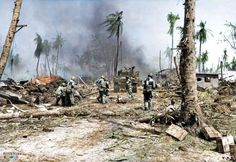 Soldiers of the US 7th Infantry Division moving a 37mm M3 anti-tank gun by hand to follow behind an M4 Sherman tank on Kwajalein, Marshall Islands, February 2, 1944. (Note the visibility panels worn...