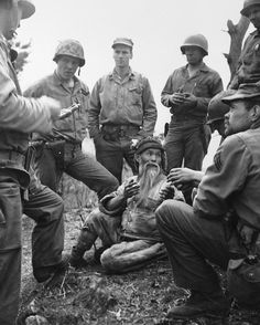 A bearded North Korean, with an American cigarette between gnarled fingers, talks with gestures to a U.S. Marine patrol on April 28, 1951 which flushed him out of the hills in North Korea while advancing ahead of tanks. He seems eager to tell his captors all he knows about the Chinese Communists who were unleashing their spring offensive. (AP Photo)