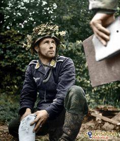 Normandy 1944. A German prisoner probably belonging to the 3. Fallschirmjäger-Division of the Luftwaffe dismantles on order of American soldiers near Saint-Georges-d'Elle.