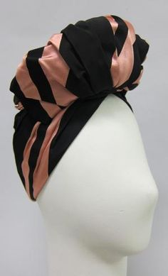 "Turban style hat of black and pink striped satin with stuffed stand up pleated pouf in front. Lined in black net with black grosgrain ribbon inner headband.Designer's label: ""Lilly Dach� Paris / 78 East 58th St. New York"""