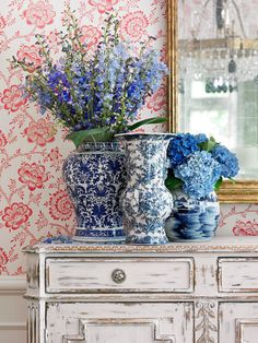 Pretty blue-and-white china looks lovely paired with the pink floral wallpaper - Traditional Home®  Photo: Emily Followill Design: Lillian August