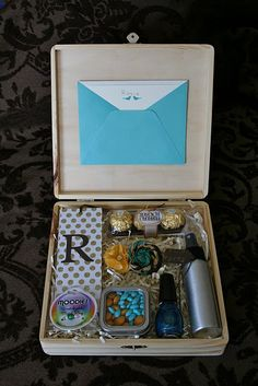 wooden box party favors: for this tween birthday, it included a monogrammed bookmark, mood ring, candies in a tin, blue nail polish, body spray, DIY hairclip flowers, chocolate, and a personal note from the birthday girl to each friend