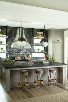 A pair of Hicks Pendants illuminate a taupe kitchen island topped with a honed black marble countertop, Pietra Gray Marble, fitted with a sink and deck mount vintage style faucet lined with taupe backless counter stools with brass bases.