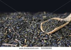 green tea on wooden spoon with black background. [blur and select focus background]