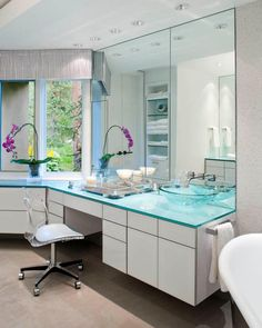 This+modern+master+bathroom+creates+sleek+lines+by+using+back-painted+glass+cabinet+and+countertops.+